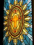 Stain Glass Religious Theme. Stain glass window in church illustrating a cross with illuminating light shinning through the window Stock Photo