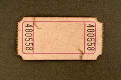 Old blank torn ticket. Old torn blank movie or raffle ticket on a mottled brown paper background Royalty Free Stock Image