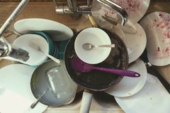 Stained Dirty Dishes In Kitchen Sink. A Messy Pile of Dirty Dishes And Utensils In Kitchen Sink royalty free stock images