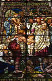 Stained Glass. A low angled image of a stained glass window from Salisbury Cathedral in wiltshire UK. Scene depicts - Suffer the Little Children to Come Unto Me Royalty Free Stock Image