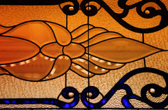 Stained glass. Detail of a stained glass window with orange light behind Royalty Free Stock Image