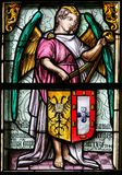 Stained Glass, Angel holding a Coat of Arms. Stained Glass in the Basilica of the Holy Blood in Bruges, Belgium, depicting an Angel holding a Coat of Arms stock photography