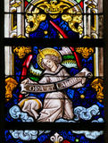 Stained Glass - Angel and Pray and Work. Stained Glass window depicting an Angel holding a sign Ora et Labore, the phrase pray and work refering to the Christian royalty free stock photo