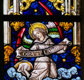 Stained Glass - Angel and Pray and Work. Stained Glass window depicting an Angel holding a sign Ora et Labore, the phrase pray and work refering to the Christian royalty free stock photos
