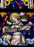 Stained Glass - Angel and Pray and Work. Stained Glass window depicting an Angel holding a sign Ora et Labore, the phrase pray and work refering to the Christian stock photography