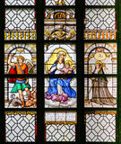 Stained Glass - Archangel Michael, Madonna and Child and Saint T. Stained Glass window in the 15th Century Elzenveld Chapel in Antwerp, Belgium, depicting the Stock Images
