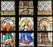Stained Glass - Archangel Michael, Madonna and Child and Saint T. Stained Glass window in the 15th Century Elzenveld Chapel in Antwerp, Belgium, depicting the Stock Photo