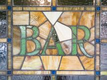 Stained Glass BAR. This photo features a stained glass window with the text showing BAR. The glass is likely over 100 years old but would seem to have been royalty free stock photos