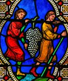 Men Carrying Grapes, symbolizing the Blood of Christ. Stained Glass in the Cathedral of Monaco, depicting Men Carrying Grapes, symbolizing the Blood of Christ stock photo