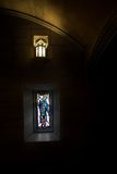 Stained glass in church. Small stained glass window and lamp in darkened church interior Royalty Free Stock Photos