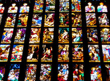 Stained glass in the church. Black glass with ornaments and images of catholic christian religious subjects, stories from Bible in Milan Cathedral, Italy Stock Image