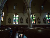 Stained glass and church pew. Glow of stained glass window on a Church pew Royalty Free Stock Images
