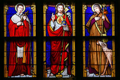 Stained Glass - Jesus Christ, Saint Roch and Saint Charles Borro. Stained Glass window in the 15th Century Elzenveld Chapel in Antwerp, Belgium, depicting Jesus Stock Photos