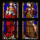 Stained Glass - Jesus Christ and Saint Roch. Stained Glass window in the 15th Century Elzenveld Chapel in Antwerp, Belgium, depicting Jesus Christ and Saint Roch Royalty Free Stock Photography