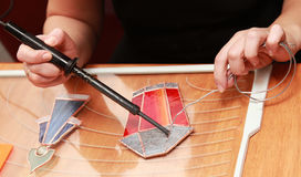Stained glass maker works with red lamp Stock Images