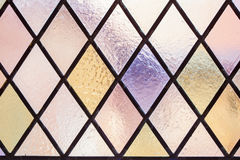 Stained glass with multi colored diamond pattern as background Stock Photo