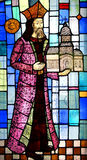 Stained glass mural. A closeup of a stained glass window depicting a man holding a church in his hand Stock Image