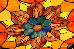 Stained glass orange flower. A beautiful bright stained glass window in orange, brown, yellow, and blue Stock Photo