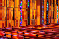 Stained glass pews. Colors from the stained glass windows pour onto the pews of the United States Air Force Academy Cadet Catholic Chapel, Air Force Academy Royalty Free Stock Image