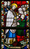 Stained Glass - Priest giving Holy Communion. Stained Glass window depicting a priest giving Holy Communion in the Cathedral of Saint Bavo in Ghent, Flanders royalty free stock images