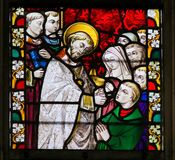Stained Glass - Priest giving Holy Communion. Stained Glass window depicting a priest giving Holy Communion in the Cathedral of Saint Bavo in Ghent, Flanders Royalty Free Stock Photo