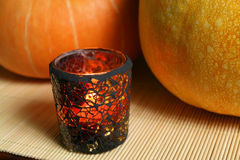 Stained glass and pumpkins. Pumpkins and candle in stained glass on bamboo mat. Halloween Stock Photo