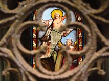 Stained Glass Resurrection Of Jesus and rusty grid. Detail of a very old stained glass window depicting the resurrection of Jesus. Photographed in an abandoned Royalty Free Stock Image