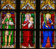 Stained Glass - Saint John the Baptist, Mother Mary and Saint Ap. Stained Glass window in the 15th Century Elzenveld Chapel in Antwerp, Belgium, depicting Saint Stock Photos