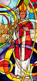 Stained glass showing the bishop. And his church in the background Stock Photography