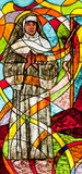 Stained glass showing the nun. And crucified Jesus in the background Stock Photography