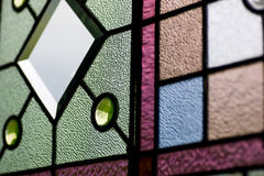Stained glass texture. Closeup of a pane of stained glass, focus on one of the round jewl-like insets Stock Images
