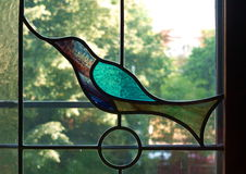 Stained glass window. Depicting a bird, with sunny garden in the background stock photos
