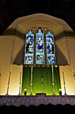 Stained glass window and altar. Closeup of stained glass window in church with candles on altar in foreground stock image