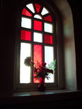 Stained glass window. A beautiful stained glass window with a flower on the window sill Stock Photography