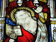 Stained glass window in church. Biblical figure with open bible on stained glass church window Stock Images