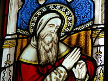 Stained glass window in church. Biblical figure on colorful stained glass window in church Stock Photography