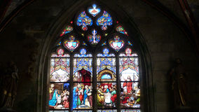 Stained glass window of a church in France. Religious scenes depicted in a beautiful stained glass window of a church in Britanny France Stock Photo