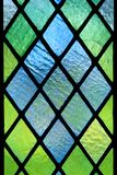 Stained Glass Window. Diagonally patterned stained translucent glass window pane detail stock photo
