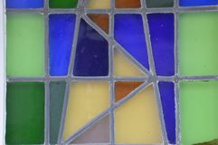 Stained-glass window in different colors green blue and yellow. A stained-glass window in different colors green blue and yellow stock images