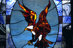 Stained Glass Window With Eagle In Chapel. A stained glass window with the depiction of an eagle is presented in this stained-glass artwork installed in a Royalty Free Stock Photos