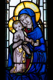 Stained glass window with mother and child. Mother and child on stained glass window royalty free stock photo