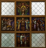 Stained glass window picturing Jesus on the Cross. Stock Photos