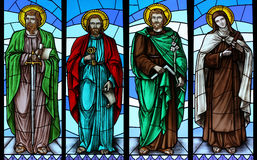 Stained glass window with saints. Stained glass church window with image of  four saints (from left to right): Paul, Peter, Joseph, Theresa Royalty Free Stock Images