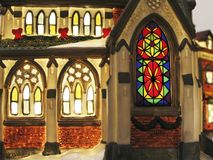 Stained Glass Windows. Light glows from the stained glass windows of a church in a miniature Christmas village display Stock Photos