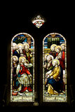 Stained glass windows, Jesus & 11 disciples. Religious stain glass windows with two panels. Stained-glass-window on a black background in a cathedral building Stock Image