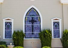 Stained Glass Windows On Side Of Church. Purple Colored Stained Glass Windows With Cross On Side Of Church Royalty Free Stock Photo