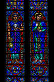 Stained Joseph and Mary. Multiple Panel Red Blue Yellow Purple and Green Stained Glass Images of Joseph of Egypt and Mary Magdalen Standing and Holding Gold and royalty free stock photo