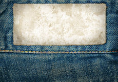 Stained leather jeans label sewed on jeans. Royalty Free Stock Images