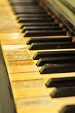 Stained Old Piano Keys. A shot of an old piano with stained ivory keys with missing ivory pieces missing that was not maintained very well Stock Photos