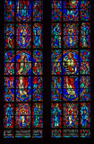 Stained Saints Lower. Multiple Panel Red Blue Yellow Purple and Green Stained Glass Images of Christian Saints In Red Robes Standing with Various Biblical stock photo